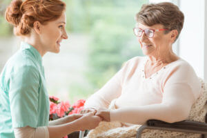 Compassionate CNA explaining a geriatric handicapped patient with dementia medical procedures while holding her hands. Assisted living house for pensioners. Side view.